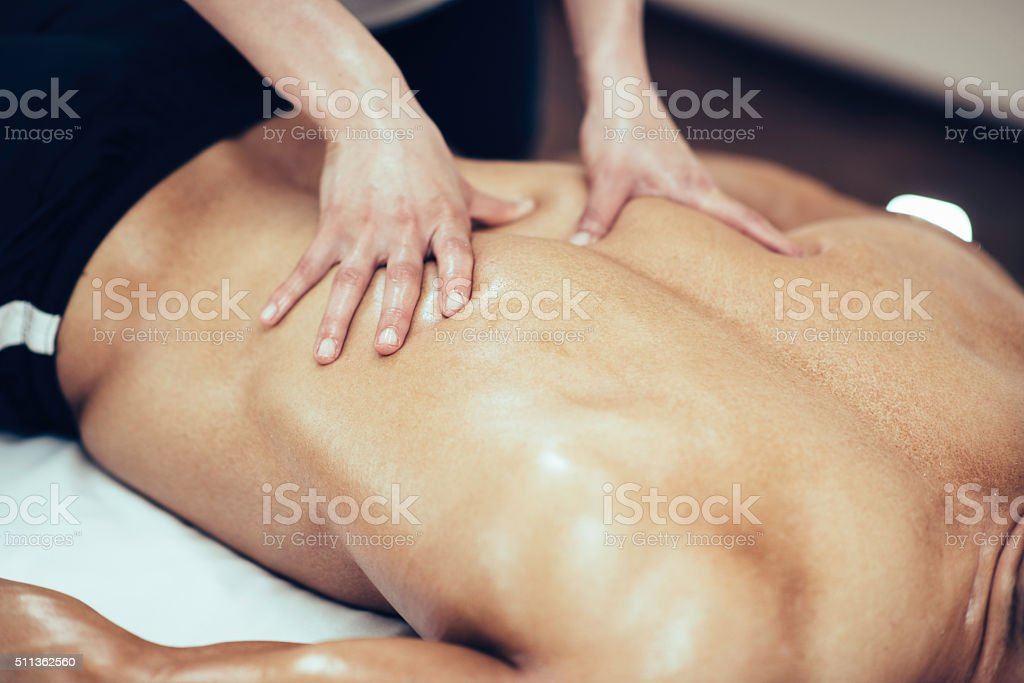 Back massage. Physical therapist massaging lower back stock photo
