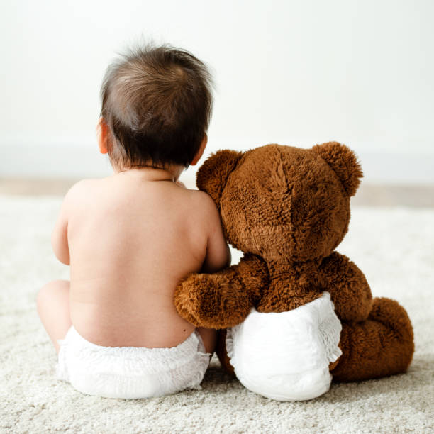 Back of a baby with a teddy bear stock photo