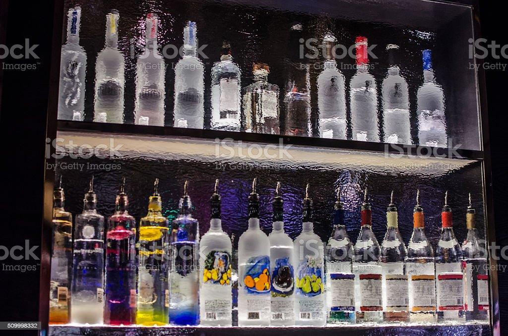 Back of a bar shelf through rippled glass stock photo