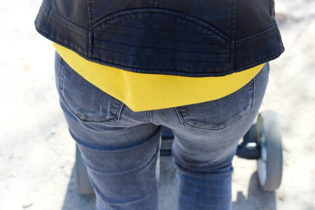 Back of a female body in tight blue jeans with pockets and a yellow sweatshirt under a leather jacket Back of a female body in tight blue jeans with pockets and a yellow sweatshirt under a leather jacket hot sexy butts stock pictures, royalty-free photos & images