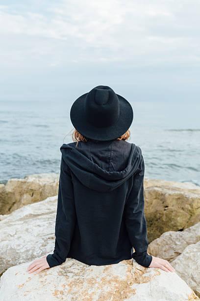 Rückseite ein Mädchen sitzt auf einem pier – Foto