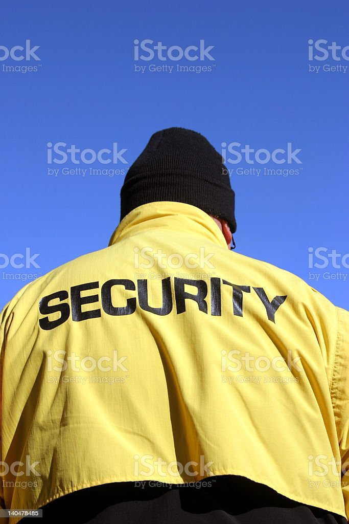 Back of a security guard wearing yellow jacket and black hat royalty-free stock photo