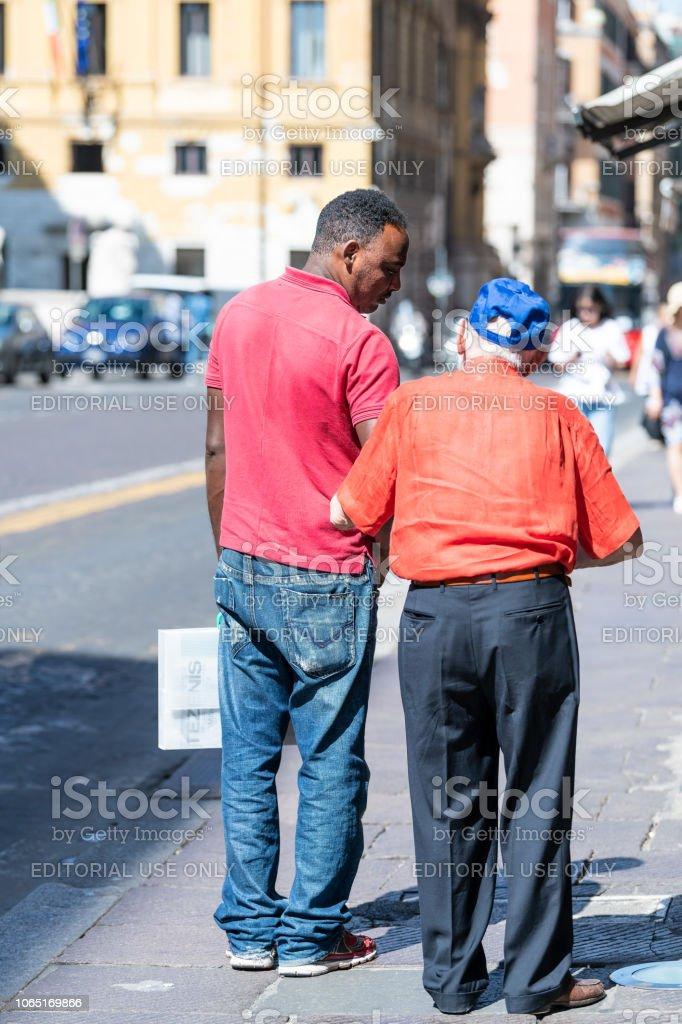 Back of African, black man helping senior old, elderly male, holding...
