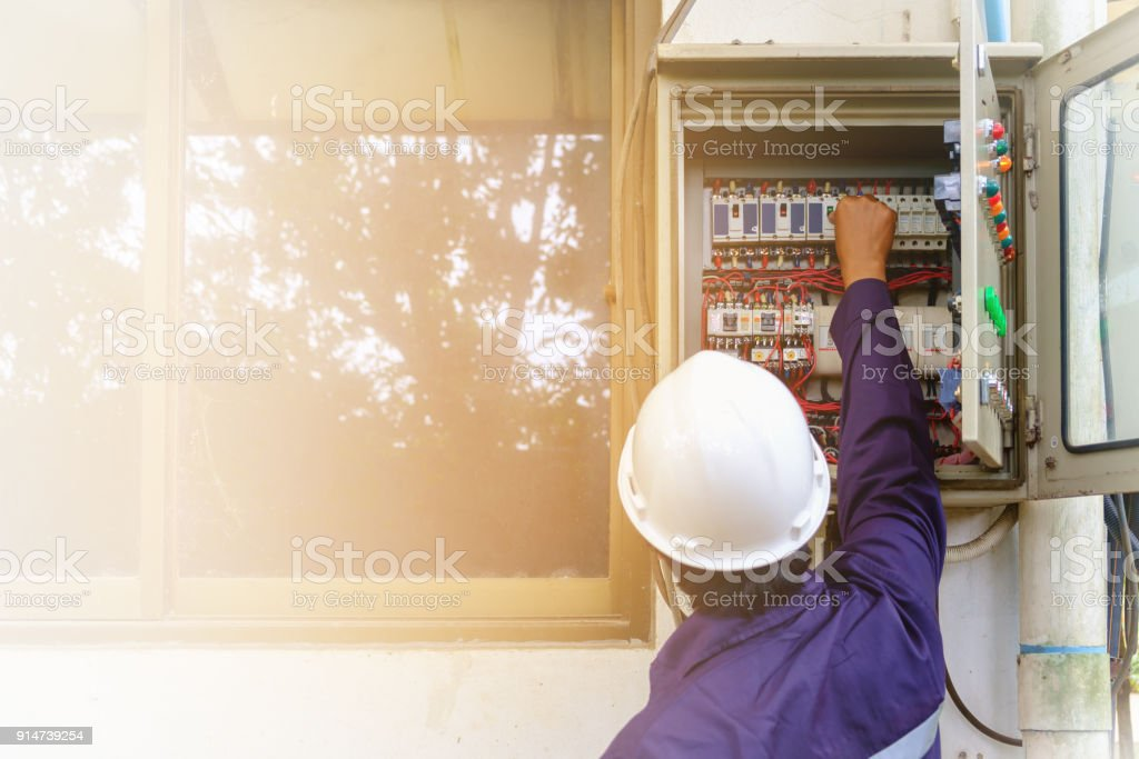 Back of asian engineer or technician in safety uniform and white security helmet turning on switch in the electrical cabinet with copy space and sun light effect for industrial concept stock photo