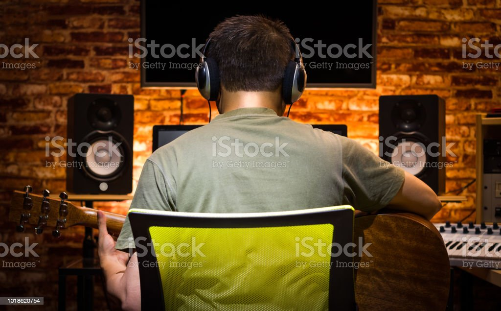 back of asian male musician recording acoustic guitar and jamming music with friends online in home studio stock photo