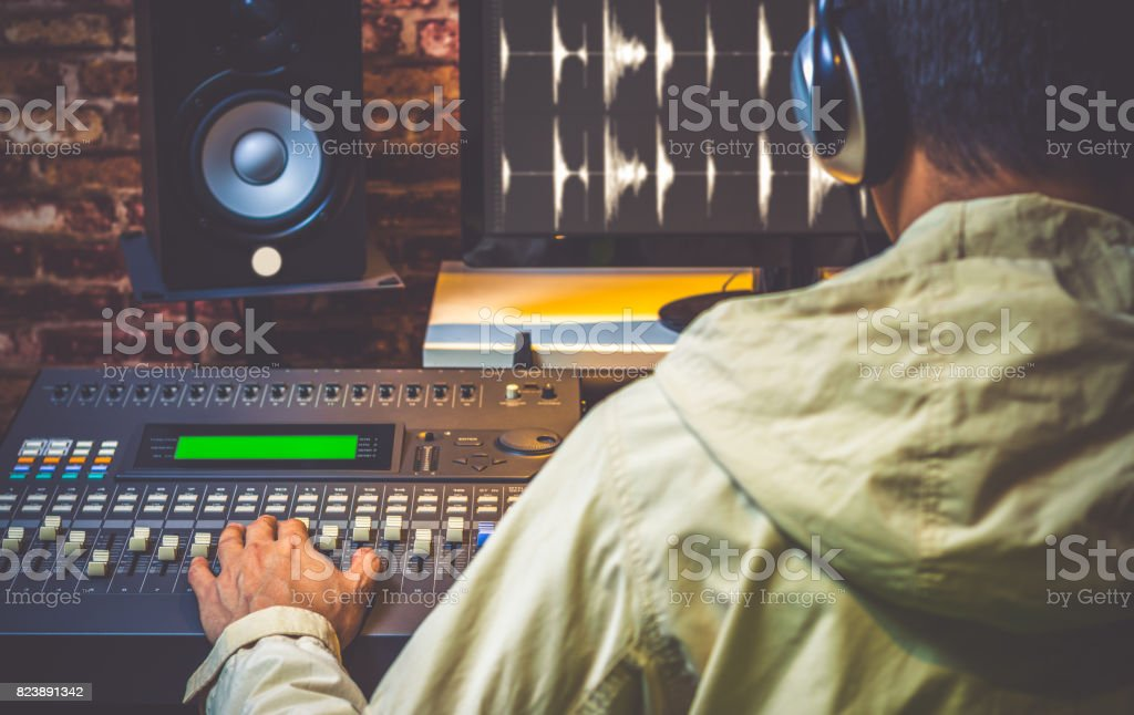 back of asian sound engineer working in digital sound editing studio, DJ working in broadcasting studio stock photo