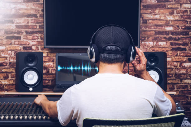 back of asian sound engineer working on audio mixing console in recording studio stock photo