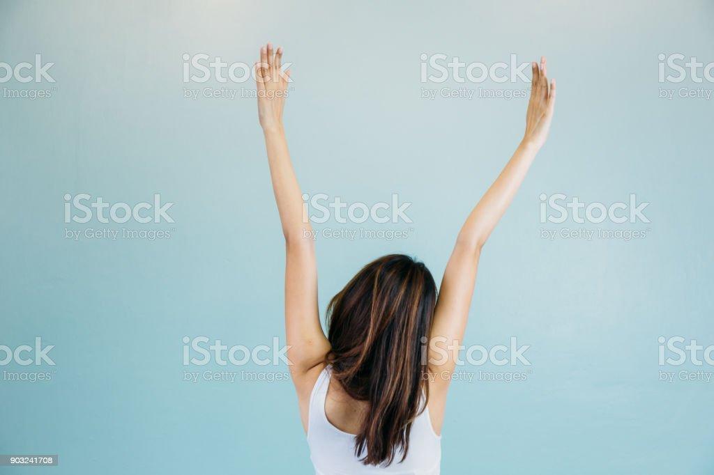 La parte posterior de la hermosa joven con los brazos alzados sobre fondo verde azul foto de stock libre de derechos