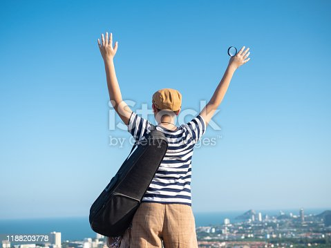 Back of boy holding violin case raising hands with the top of city view, lifestyle concept.