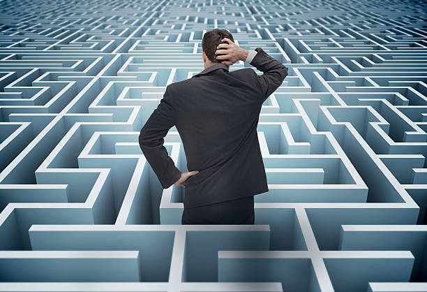 Back of businessman getting lost in a maze stock photo