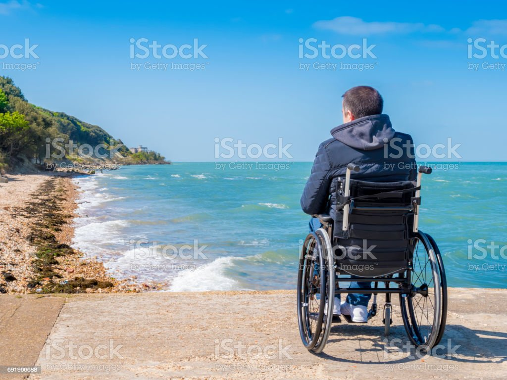 Back of disabled man in wheelchair at beach stock photo