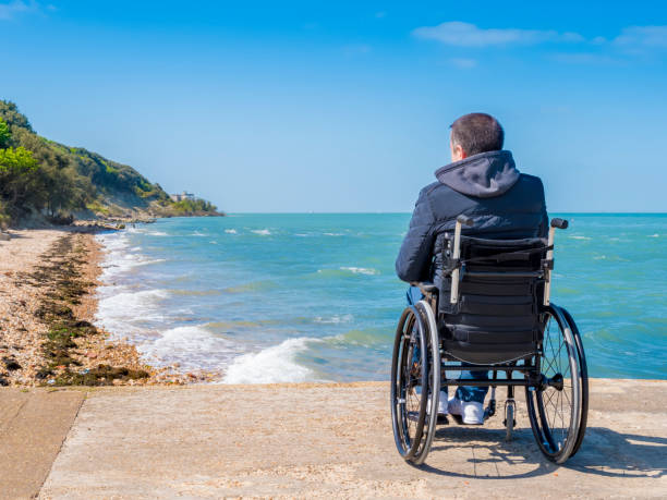 Back of disabled man in wheelchair at beach Back of alone disabled young man in wheelchair at beach. paralysis stock pictures, royalty-free photos & images