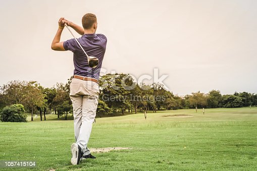 istock Back of golfer hitting ball on green field with copy space. 1057415104