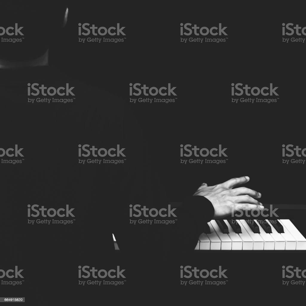 back of male asian musician playing piano stock photo