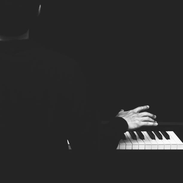 back of male asian musician playing piano back of male asian musician playing piano, black and white pianist stock pictures, royalty-free photos & images