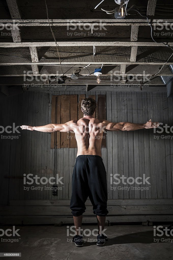 Back of muscular man standing in a grungy workout room royalty-free stock photo