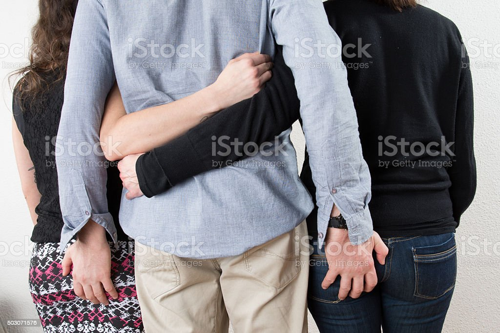 Back of one man with two women on each side stock photo