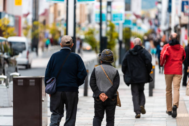 Parte traseira dos pares sênior dos turistas dos povos que andam na estrada da rua do passeio - foto de acervo