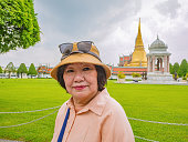 Back of Senior Tourist in Wat Phrakeaw Temple  with Cloud sky.Wat Phrakeaw Temple is the main Temple of bangkok Capital of Thailand