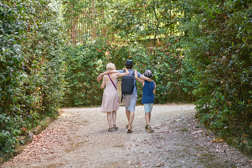Back of small family with mother and two sons embracing each other while walking on the path of a park between big green bushes