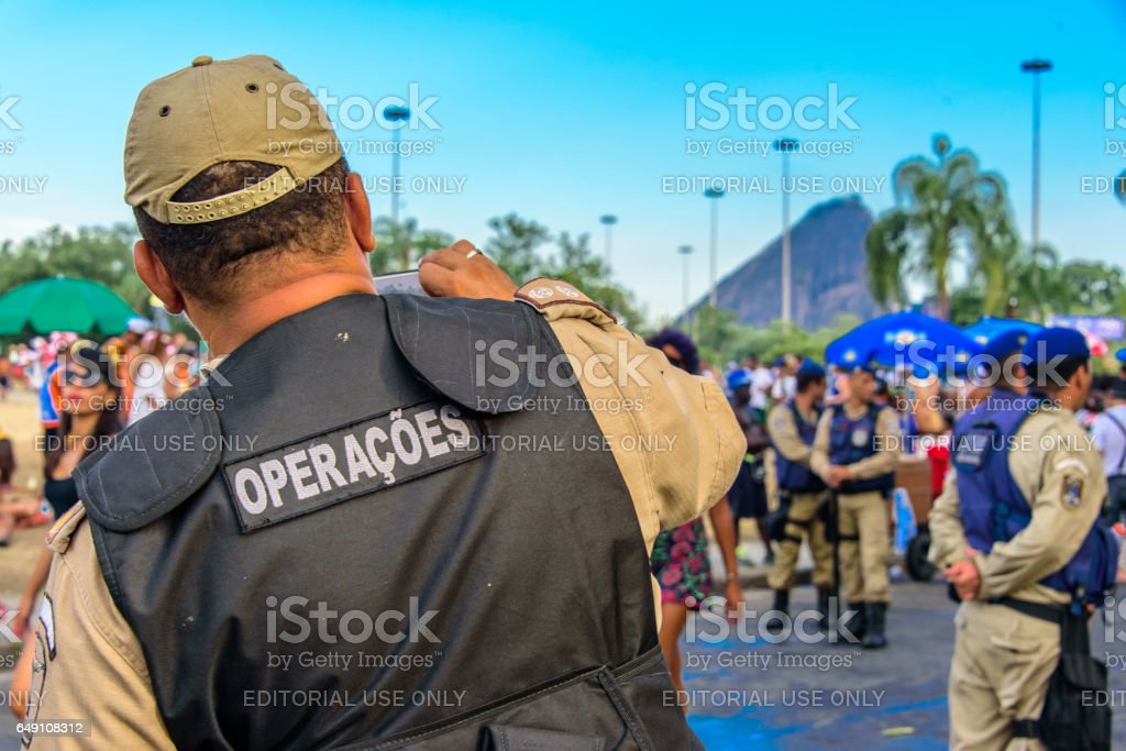 Back of the policeman taking pictures of costume people at Bloco Orquestra Voadora in Flamengo Park, Carnaval 2017 stock photo