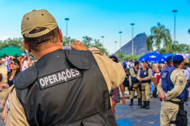 detrás del policía tomar fotografías de personas de traje en el bloco orquesta voadora en parque de flamengo, carnaval 2017 - feliz dia del policia fotografías e imágenes de stock