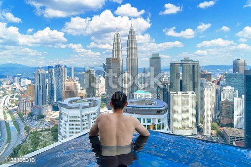 istock Back of tourist in a swimming pool on rooftop with Kuala Lumpur downtown view and blue sky. Malaysia travel trip in vacation and holidays concept in Asia. Skyscraper and high-rise buildings at noon. 1133108010