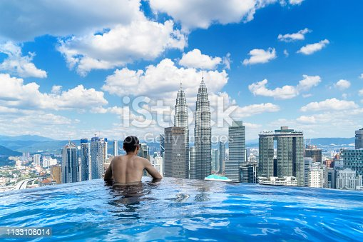 istock Back of tourist in a swimming pool on rooftop with Kuala Lumpur downtown view and blue sky. Malaysia travel trip in vacation and holidays concept in Asia. Skyscraper and high-rise buildings at noon. 1133108014
