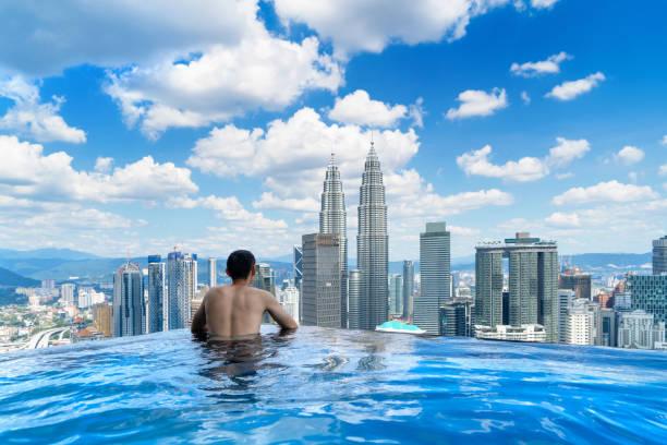 쿠 알라 룸 푸 르 시내 전망과 푸른 하늘 옥상에 수영장에서 관광의 뒤쪽. 아시아에서 휴가 및 휴일 개념에 말레이시아 여행 여행. 마천루와 고층 건물 정오. - 쿠알라룸푸르 뉴스 사진 이미지