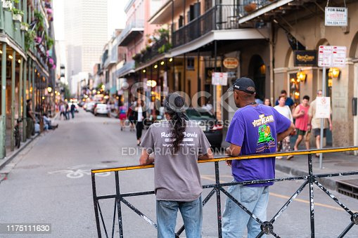 889246424istockphoto Back of two local men standing on Bourbon street road in evening with people walking in blurry background of Louisiana city 1175111630