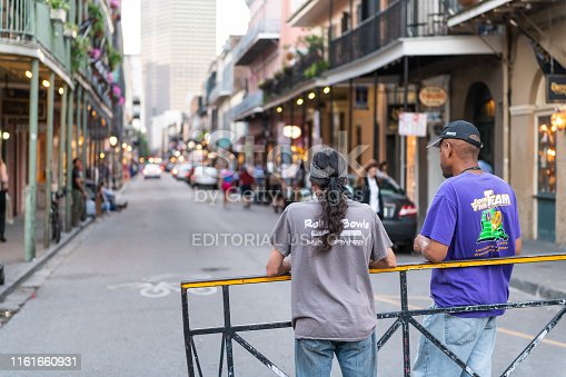 889246424istockphoto Back of two local men standing on Bourbon street road in New Orleans 1161660931