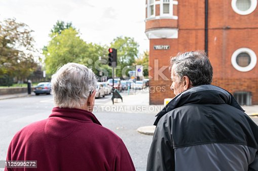 istock Back of two men pedestrians waiting for red traffic light on street road in morning in Pimlico or Chelsea 1125995272