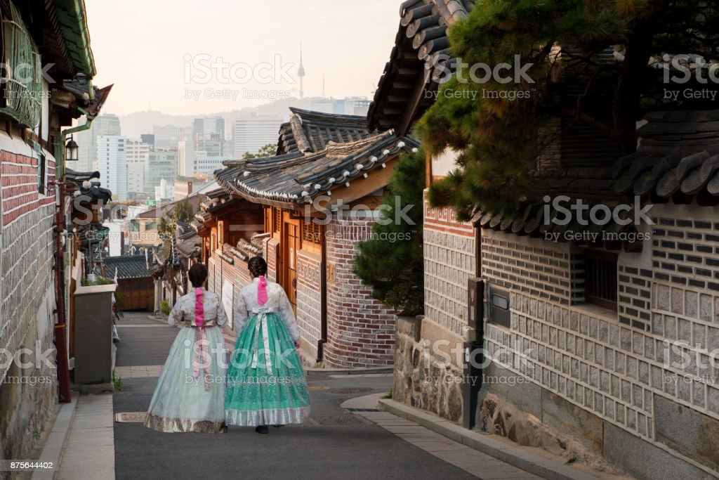 Back of two women wearing hanbok walking through the traditional style houses of Bukchon Hanok Village in Seoul, South Korea. stock photo