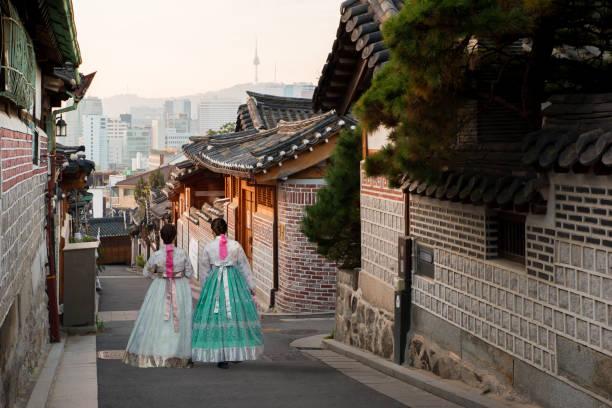 裏北村韓屋村のソウル, 南朝鮮の伝統的な様式の家を歩く韓服を着て 2 人の女性。 - ソウル ストックフォトと画像