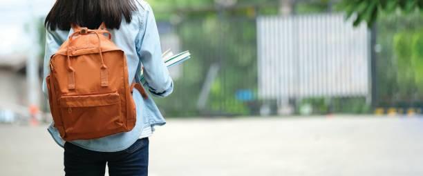para trás do estudante universitário com a trouxa ao ir à faculdade andando da rua, adolescente no terreno, conceito da instrução - universidade - fotografias e filmes do acervo