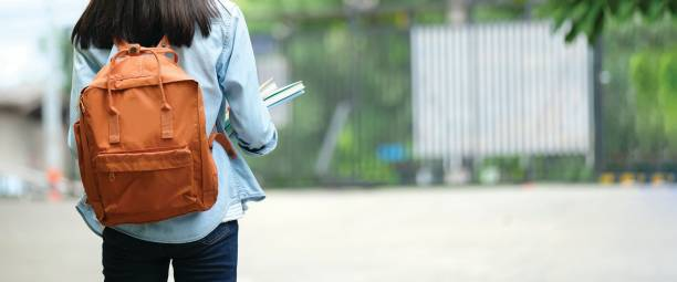 Back of university student with backpack while going to college by walking from street, teenager in campus, education concept stock photo