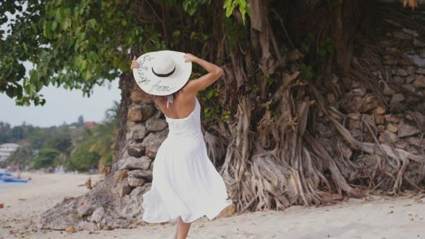 rückseite blick auf junge elegante frau mit langen haaren in weißen drees am tropischen strand - drees und sommer stock-fotos und bilder