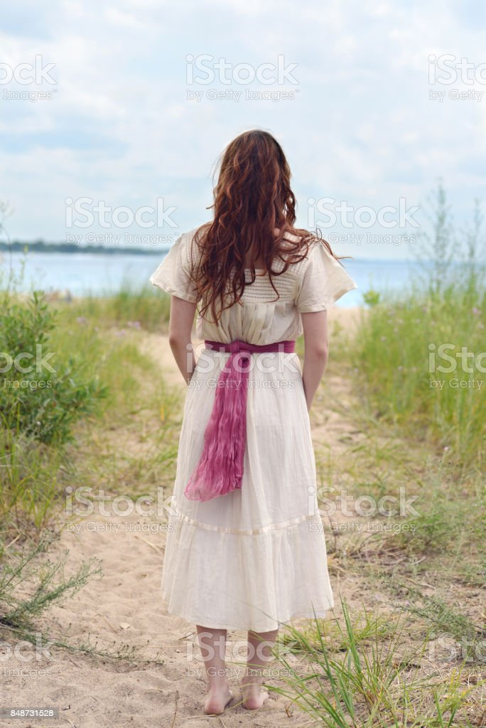 back of vintage redhead woman at the beach with bare feet stock photo