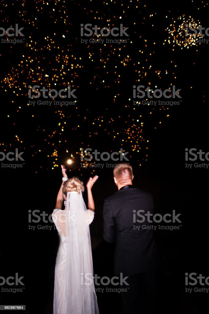Rückseite des Hochzeitspaar am Nachthimmel mit Feuerwerk suchen. – Foto