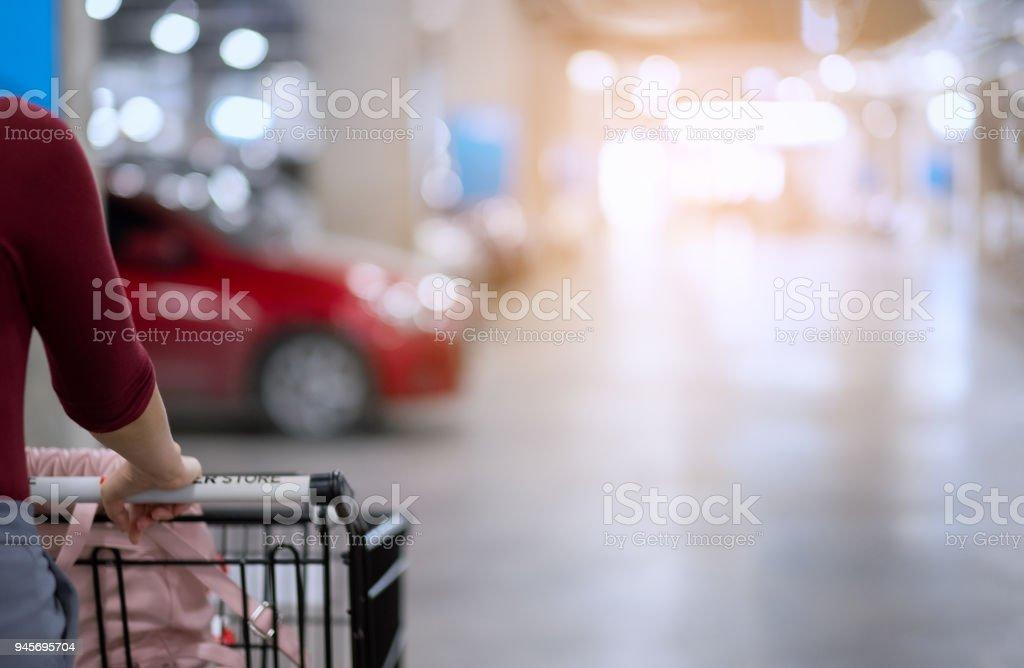 Rückseite der Frau mit Warenkorb Warenkorb verschieben und suchen Sie ihr Auto in Auto Weichzeichnen Parkplatz des Einkaufszentrums mit Weichzeichner und Beleuchtung Hintergrund – Foto