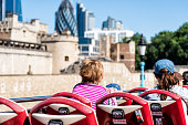 istock Back of women tourists looking at city cityscape view, tower fortifications wall buildings on street road double decker red Big Bus in center of downtown 994753642