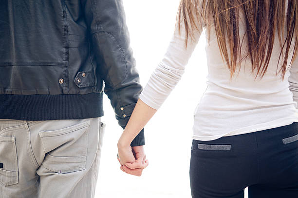 Back of Young couple holding hands stock photo