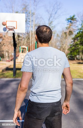 istock Back of young fit muscular man throwing basketball into hoop 653890944
