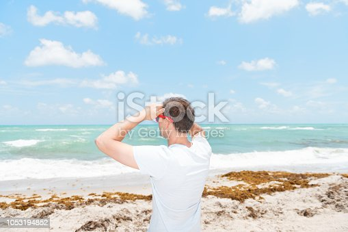 Back of young man in sunglasses standing on sand, sandy beach in Miami, Florida by ocean, sea water, waves on sunny day with blue sky, seaweed, two hands holding on forehead