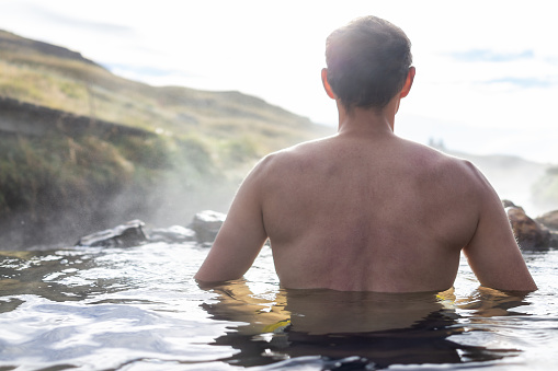 istock Back of young man swimming bathing in Hveragerdi Hot Springs on trail in Reykjadalur, morning day in south Iceland, golden circle, rocks 1073411740