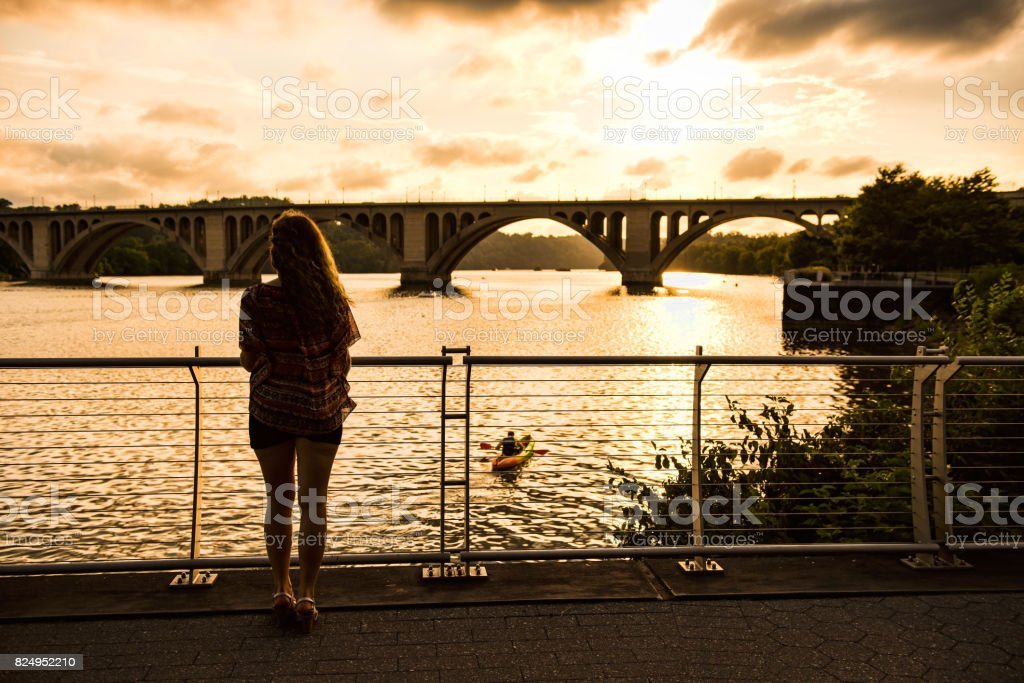 Back of young woman looking over potomac river with Francis Scott Key Bridge during sunset stock photo