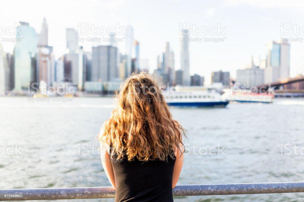 Parte traseira do jovem fora ao ar livre em NYC New York City Brooklyn Bridge Park pelo rio east, trilhos, olhando a vista do horizonte da paisagem urbana - foto de acervo