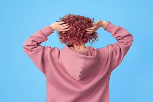 Back of young woman with pink hair
