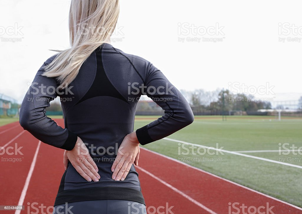 Back Pain. Athletic fitness woman rubbing lower back. stock photo