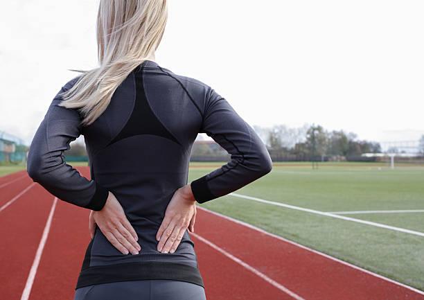 back pain. athletic fitness woman rubbing lower back. - parte inferior - fotografias e filmes do acervo